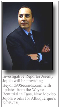 Photo of Jeremy Jojola in suit with arms folded.