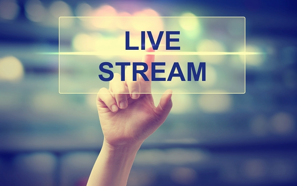Finger on hand touching text stating Live Stream.