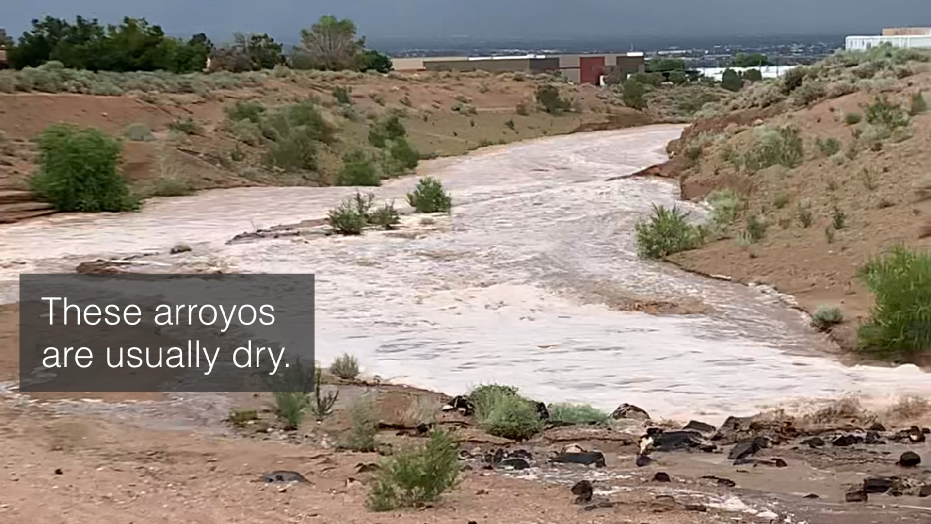 """Water rushing in a desert arroyo. Text over image states, """"These arroyos are usually dry."""""""