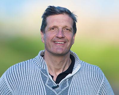 Headshot of Christian Sasse smiling outdoors.